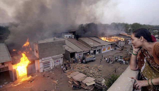 AHMEDABAD, INDIA: (FILES) This picture taken 28 February 2002 shows Ahmedabad resident Jaiwantiben watching a wood market burning after it was set ablaze by Muslims that fled the Lathi bazar area in Ahmedabad. SEBASTIAN D'SOUZA/AFP/Getty Images)