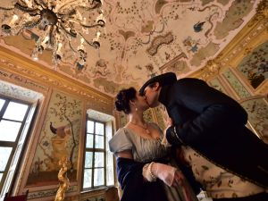 People dressed-up in eighteenth century costumes as Pauline Bonaparte and Camillo Borghese, kiss to celebrate Valentine's Day in one of the rooms of the royal hunting lodge and residence (Palazzina di caccia) built for the Royal House of Savoy in Stupinigi, 10 kms southwest of Turin, northern Italy, on February 14, 2016.