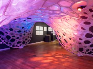 Installation view of the PolyThread knitted textile pavilion, designed by Jenny E. Sabin, commissioned for Beauty—Cooper Hewitt Design Triennial. Photo by Matt Flynn © 2016 Cooper Hewitt, Smithsonian Design Museum. PolyThread knitted textile pavilion, 2015–16 Designed by Jenny E. Sabin, Jenny Sabin Studio Design Team: Martin Miller, Charles Cupples Fabricated by Shima Seiki, WHOLEGARMENT Engineering Design by Arup Fabric finishing by Andrew Dahlgren Final finishing, sewing, and assembly by All Sewn Together 3D seamless Whole Garment digitally knit cone elements, photoluminescent, solar active and drake yarns; twill tape; aluminum armature Commissioned by Cooper Hewitt, Smithsonian Design Museum
