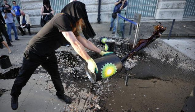 A protester belonging to a group of artists calling themselves 'The Good Crude Britannia', who want the Tate to cut its ties with British Petroleum (BP), throws a substance thought to be molasses on the floor outside, the Tate Britain on June 28, 2010, as the gallery holds its summer party.