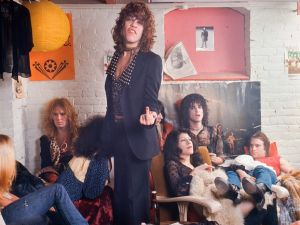 The New York Dolls in their dressing room at Paradiso, Amsterdam, Netherlands, 7th December 1973. L-R Arthur Kane (back left against wall), David Johansen (centre, raising middle finger), Johnny Thunders (part obscured behind Johansen), Sylvain Sylvain (leaning against wall in front of Rolling Stones poster), Jerry Nolan (lying back, wearing red t-shirt). (Photo by Gijsbert Hanekroot/Redferns)