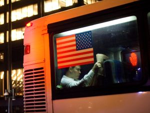 NEW YORK, NY - NOVEMBER 15: A man reading a newspaper in the back of an express bus passes Zuccotti Park as protesters waited for the re-opening of the park on November 15, 2011 in New York City. Police had removed the protesters from the park early in the morning. A judge ruled that protesters are allowed back to the park but won't be allowed to camp there. Hundreds of protesters, who rallied against inequality in America, have slept in tents and under tarps since September 17 in Zuccotti Park, which has since become the epicenter of the global Occupy movement. The raid in New York City follows recent similar moves in Oakland, California, and Portland, Oregon. (Photo by Michael Nagle/Getty Images)