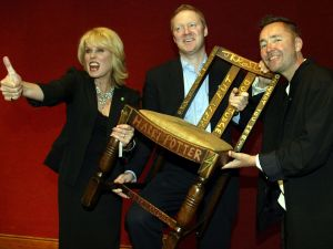 Actress Joanna Lumley (L), Miles Apthorp (C) and actor Rory Bremner (R) pose with the JK Rowling 'Harry Potter' chair at the 2002 Chairish the Child auction