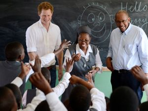 Britain's Prince Harry (L) flanked by Sister Victoria Mota (C) and Prince Seeiso, the younger brother of King Letsie of Lesotho, interacts with pupils at the Kananelo Centre for the Deaf on February 27, 2013 in Maseru. Prince Harry visited his charity projects in Lesotho on February 27 during his return visit to the southern African kingdom. The projects work with Sentebale, an organisation which Harry set up with Seeiso. The third-in-line to the British throne will travel to Johannesburg in neighbouring South Africa in the afternoon for a fund-raising gala dinner. AFP PHOTO / STEPHANE DE SAKUTIN