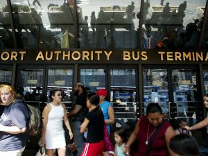 Stranded travellers gather outside the closed Port Authority Bus Terminal during a massive blackout August