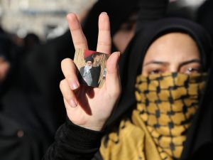An Iranian student shows flashes the sign of victory holding a portrait of Iran's Supreme Leader Ayatollah Ali Khamenei during a demonstration on February 18, 2015, near the Swiss embassy in Tehran, in solidarity with the three Muslim American students murdered last week in the North Carolina university town of Chapel Hill. The three victims were shot dead on February 10 in their home in North Carolina, allegedly by neighbour Craig Stephen Hicks, 46, whose Facebook page espoused anti-religious views.