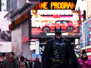 """Batman"" smiles as he waits for customers at Times Square in New York on February 27, 2015."