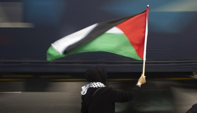A woman holds a Palestinian flag as a truck passes by.