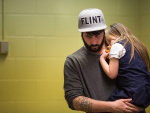 Matt Hopper of Flint, Michigan holds and comforts Nyla Hopper after a blood test for lead.
