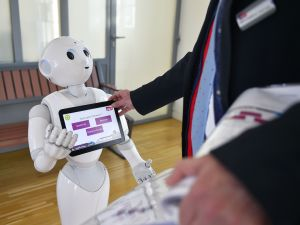 """TO GO WITH AFP STORY BY JEAN LIOU A SNCF agent makes settings on """"Pepper"""", a humanoid robot which delivers information to users of the French railway company SNCF, on March 2, 2016 at the Nort-sur-Erdre train station, western France. Made by French firm Aldebaran, Japanese group SoftBank's subsidiary, Pepper has been installed in December in three stations in the Pays de la Loire region. / AFP / LOIC VENANCE"""