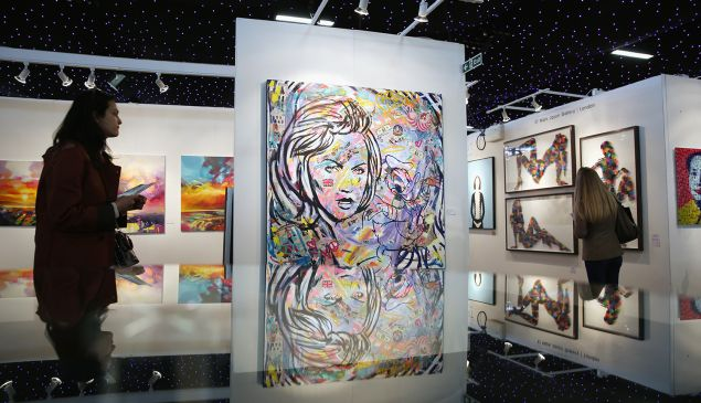 Members of the public walk through gallery spaces at the 'Affordable Art Fair' in Battersea Park on March 11, 2016 in London.