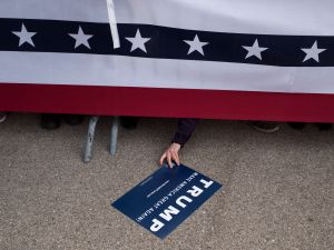 An attendee reaches under the security rail to reach for a campaign sign that was dropped at a campaign rally for Republican Presidential candidate Donald Trump on March 12, 2016 in Vandailia, Ohio. Today was the first rally after violence broke out in a Trump Rally in Chicago yesterday which canceled the rally.