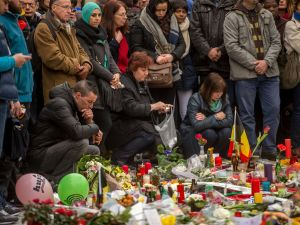 People gather at a makeshift memorial in front of Brussel's Stock Exchange.