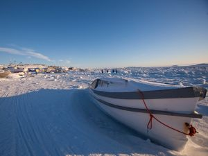 A boat sits along the frozen shoreline in Iqaluit, Canada.