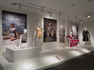 Overview of gallery featuring a Claire McCardell swimsuit, Carolyn Schnurer play suit, Mainbocher suit, Claire McCardell dress, and Christian Dior New York coat, collection of The Museum at FIT.