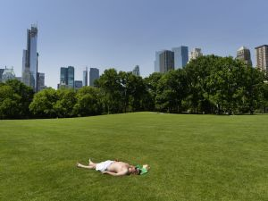 A man takes advantage of the hot weather to sun bathe in the Sheep Meadow in Central Park on May 30, 2013 in New York City. (