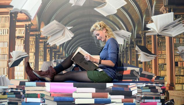 FRANKFURT AM MAIN, GERMANY - OCTOBER 09: A woman pose for a photo in front of photowall with motiv of a phantasy library at the 2013 Frankfurt Book Fair on October 9, 2013 in Frankfurt, Germany. This year's fair will be open to the public from October 9-13 and the official partner nation is Brazil.