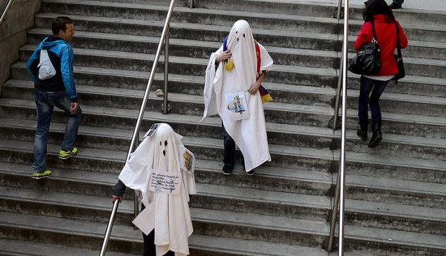 Two FC Basel fans disguised as ghosts leave St. Jakob Stadium prior to the UEFA Europa League quarter-final first leg football match FC Basel vs Valencia CF on April 3, 2014 in Basel. Swiss club FC Basel must play their Europa League quarter-final first leg clash against Valencia behind closed doors after being punished for the violent behavior of their fans. UEFA also fined FC Basel 107,000 euros ($147,500) after objects, including cigarette lighters, were thrown on to the pitch in their last-16 clash against Salzburg last week with the referee halting the game for 10 minutes. AFP PHOTO / FABRICE COFFRINI