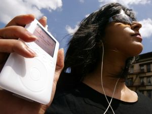 NEW YORK - JULY 15: Keeno Ahmed listens to her iPod mini digital music player July 15, 2004 in New York City. Apple Computer Inc. reported quarterly earnings that more than tripled, fueled by sales of its iPod digital music players.