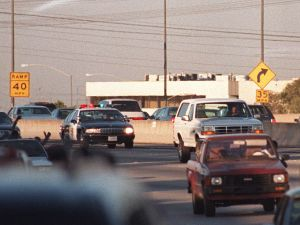 Motorists wave as police cars pursue the Ford Bronco (white, R) driven by Al Cowlings, carrying fugitive murder suspect O.J. Simpson, on a 90-minute slow-speed car chase June 17, 1994 on the 405 freeway in Los Angeles, California.