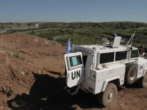 A peacekeeper of the United Nations Disengagement Observer Force (UNDOF) holds a position near the border with Syria in the Israeli-occupied sector of the Golan Heights on April 17, 2016.