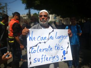 A Palestinian whose home was destroyed during 50-day war between Israel and Hamas militants in the summer of 2014 holds a banner during a protest in front of United Nations Development Programme (UNDP) headquarters, in Gaza City on April 20, 2016, against the ban of private imports of cement to the Palestinian enclave. / AFP / MOHAMMED ABED