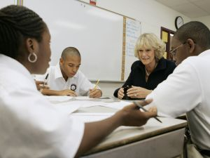 Camilla, the Duchess of Cornwall, sits in a classroom next to Denzell Grimes in a classroom in Washington D.C.