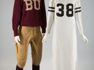 Man's football knickers with a maroon wool knit sweater with letters BU knit on center front next to a football jersey long sleeve evening dress