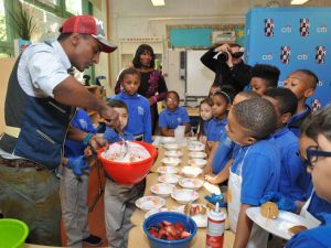 Marcus Samuelsson shows children at East Harlem Scholars Academy how to make yogurt parfaits