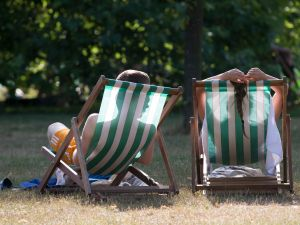 A couple relax on deckchairs in the warm weather in Hyde Park on July 18, 2014 in London, England.