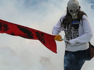 A person holds a flag as police uses tear gas and water cannon on October 7, 2014 in Ankara against demonstrators who protest against attacks launched by Islamic State insurgents targeting the Syrian city of Kobane and lack of action by the government. Fresh air strikes by the US-led coalition hit positions held by Islamic State jihadists in the southwest of the key Syrian border town of Ain al-Arab (Kobane), according to an AFP journalist just across the border in Turkey. The strikes came a day after the extremists pushed into Kobane, seizing three districts in the city's east after fierce street battles with its Kurdish defenders. AFP PHOTO/ADEM ALTAN