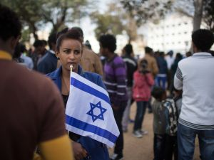 An African woman holds an Israeli flag as thousands of African migrants take part in a rally on January 7, 2014 in Tel Aviv, Israel. Tens of thousands of African asylum seekers are protesting against a law allowing authorities to keep them in open-ended detention until the resolution of their asylum requests are granted, they are deported or they volunteer to leave the country.