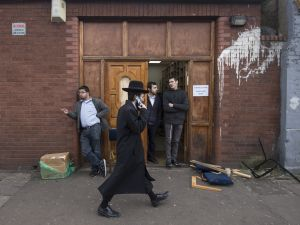 An Orthodox jew talks on his mobile phone as he walks past the Ahavas Torah synagogue in the Stamford Hill area of north London on March 22, 2015. Six people have been arrested after a group broke into a synagogue in a heavily Jewish area of north London, police said Sunday, describing the incident as anti-Semitic. Police were called to the synagogue in Stamford Hill, home to Europe's largest strictly Orthodox Jewish community, in the early hours of Sunday to reports of a disturbance. AFP PHOTO / NIKLAS HALLE'N