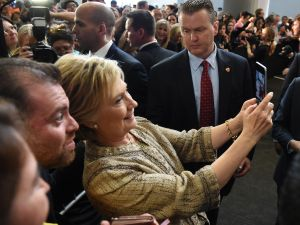 Hillary Clinton takes a selfie with a fan during a campaign rally at the Southwest College