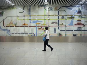A woman walks past a wall painting of the Beijing subway system inside at a station in Beijing on May 9, 2016. As part of measures to try to limit the size of Beijing and relieve traffic congestion and reduce air pollution, some Beijing Subway lines or other commuter transport lines will expand to cities in Hebei. / AFP / WANG ZHAO