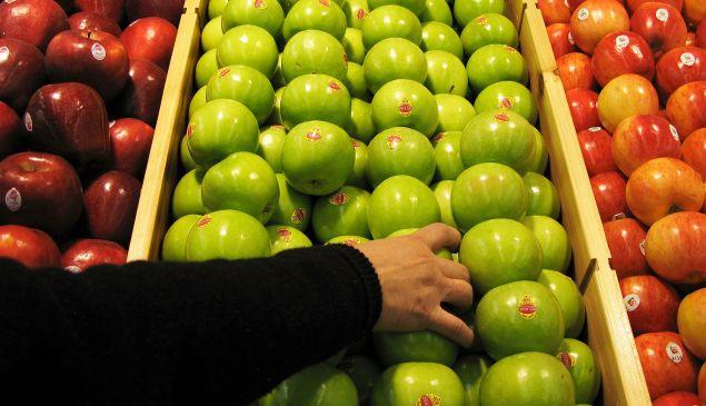 A shopper chooses granny smith apples.