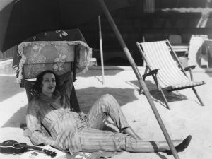 circa 1930: Vampish American actress Carmel Myers (1899 - 1980), who appeared such MGM films as 'A Certain Young Man', relaxing outdoors with a ukelele and a sunshade.