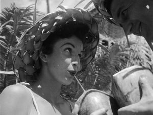 circa 1955: Bert and Ellie Lang, a young American couple on their honeymoon in Hawaii sample a local speciality - coconut cocktail drunk straight out of the shell.