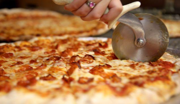 Arlet Lagoa cuts a pizza into slices at Miami's Best Pizza restaurant.
