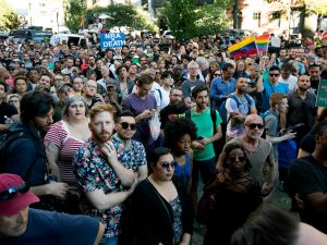 People gather outside of the Stonewall Inn as a vigil is held following the massacre that occurred at a gay Orlando nightclub early Sunday morning.