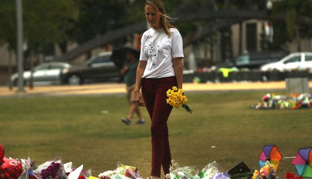 A woman visits a memorial for those killed at the Pulse nightclub last Saturday night on June 16, 2016 in Orlando, Florida. Omar Mir Seddique Mateen shot the victims in what appears to be an ISIS inspired attack in which 49 people were killed early Sunday and 53 people were wounded.