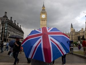 A pedestrian shelters from the rain beneath a Union flag themed umbrella as they walk near the Big Ben clock face and the Elizabeth Tower at the Houses of Parliament in central London on June 25, 2016, following the pro-Brexit result of the UK's EU referendum vote.