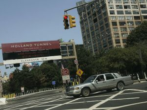 Police arrest three individuals carrying weapons outside the Holland Tunnel.