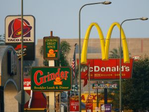Signs for Taco Bell, Grinder, McDonalds, Panda Express fast-food restaurant line the streets in the Figueroa Corridor area of South Los Angeles on July 24, 2008, Los Angeles, California.
