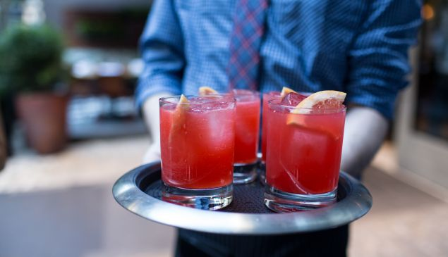 """A waiter brings out the Perche Aspettare— Campari, fresh grapefruit juice and prosecco—at the party for """"Spritz: Italy's Most Iconic Aperitivo Cocktail, with Recipes"""" at Sessanta."""