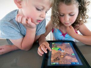 These kids may be engrossed in their iPad, but a new book says the tablet is harmful to their developing brains.