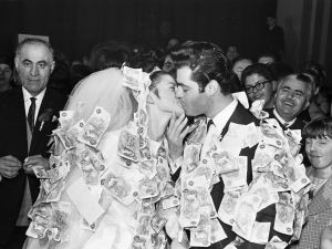 23rd November 1965: Daniel Americanos and his bride at their reception at Stoke Newington town hall, London. According to Greek tradition guests pin money on to the clothes of the happy couple.