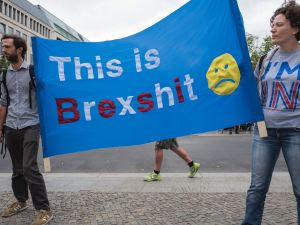 "Demonstrators hold a banner reading ""This is Brexshit"" during a protest near Britain's embassy in Berlin on July 2, 2016. Some 20 demonstrators, mostly British expats living in Berlin, protested against the outcome of the recent ""Brexit"" referendum, expressing their allegiance to the EU. / AFP / John MACDOUGALL"
