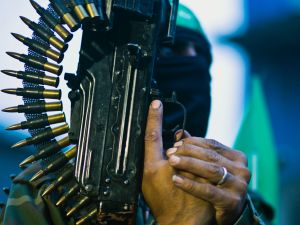 A member of the Ezzedine al-Qassam Brigades, the military wing of the Palestinian Islamist movement Hamas holds his weapon during a rally to mark the 12th anniversary of the death of assassinated Hamas spiritual leader Sheikh Ahmed Yassine on March 23, 2016 outside his home in Gaza city. / AFP / MAHMUD HAMS