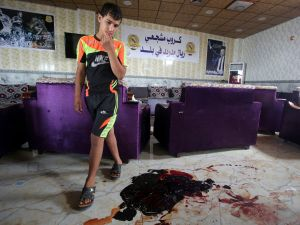 TOPSHOT - An Iraqi boy walks past the blood stains and debris at a cafe, that was popular with local fans of Spain's Real Madrid football club, in the Balad area, north of the capital Baghdad, on May 14, 2016, a day after a deadly raid claimed by Islamic State group militants. At least 16 people were killed and 30 wounded, including several members of the security forces, in the attack in the town of Balad and the ensuing chase, officials said. / AFP / AHMAD AL-RUBAYE